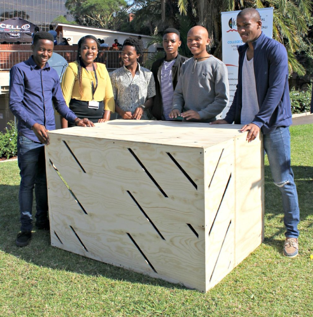 Architecture students seen with their chicken coops, created for the Green Camp gallery project.